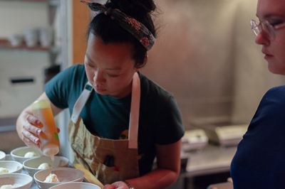 Francesca Hong, Chef at Morris Ramen in Madison, WI, preparing a dish during the 2019 Feast: A Performative Art Dinner by artist Kel Mur.